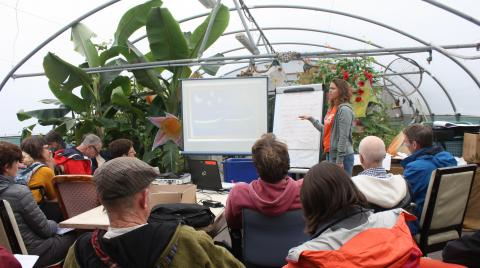 Students gather around a presentation with plants in the background