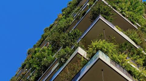 Building with green plants at every level against a blue sky.