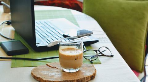 Coffee sitting next to a laptop on a desk with a green chair in the background.