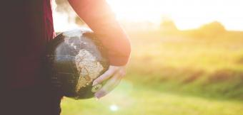 Person Holding a Globe to their side while sunshines in the background