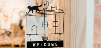 Welcome sign in the outline of a house with a cat on top