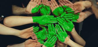 Hands being painted into a green heart