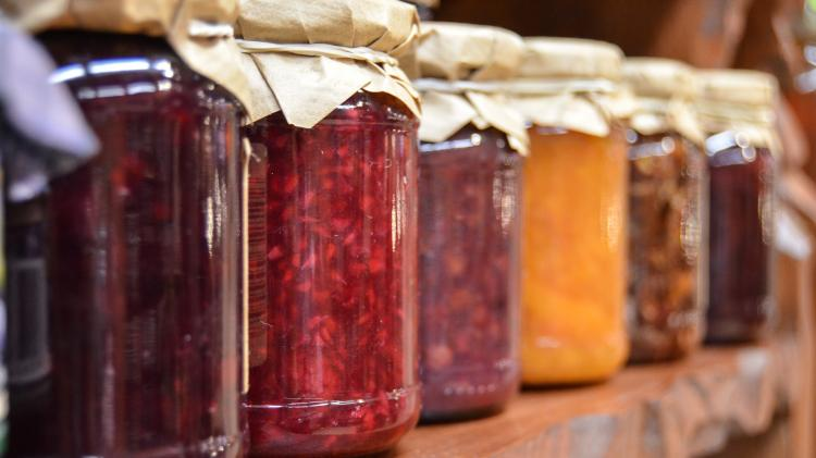 Jars of jam lined up on a shelf