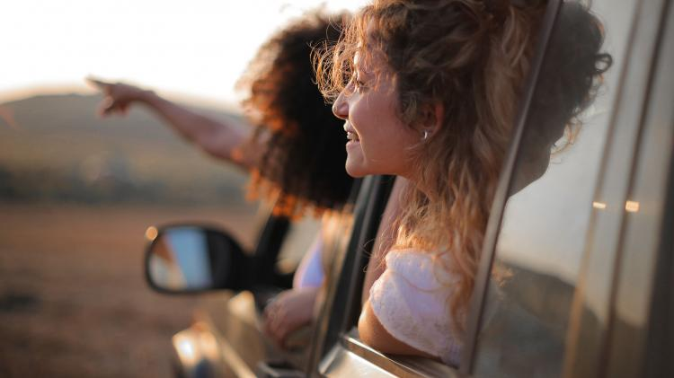 Two women lean out a car window on a roadtrip