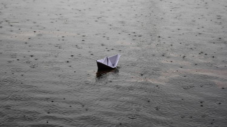 Small Paper Boat Floating in Rain Water