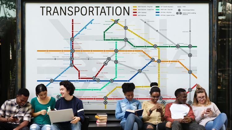 Several people sitting on a bench in front of a transportation map.