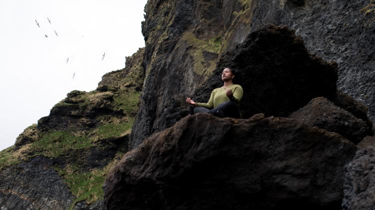 Person in Zen pose outside a cave with sky behind them.