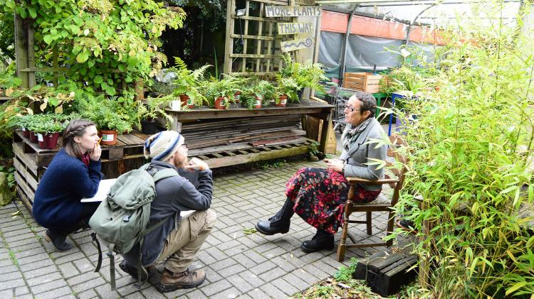 Two people squat while listening to a person sitting in a chair talking. They are all in a garden.