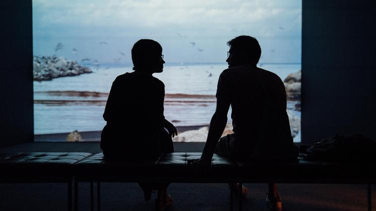 Silhouettes of two people talking in front of a picture of nature.