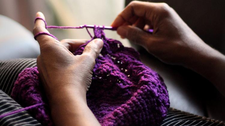 Hands knitting a purple hat